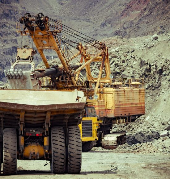 Heavy mining trucks and excavator working on the iron ore opencast mining facility